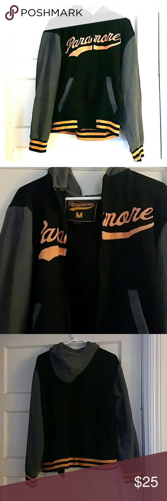 Paramore Varsity Style Zipup Hoodie Size Medium This hoodie has an easy street style. Whether you love Paramore or not, the hoodie is super comfy. Worn with love but still in good condition. The hood is double layered providing extra warm on colder nights out with friends or sotting by a fire. Gray, Orange lettering, and black body. Drawstrings missing, pictured above. Paramore Jackets & Coats