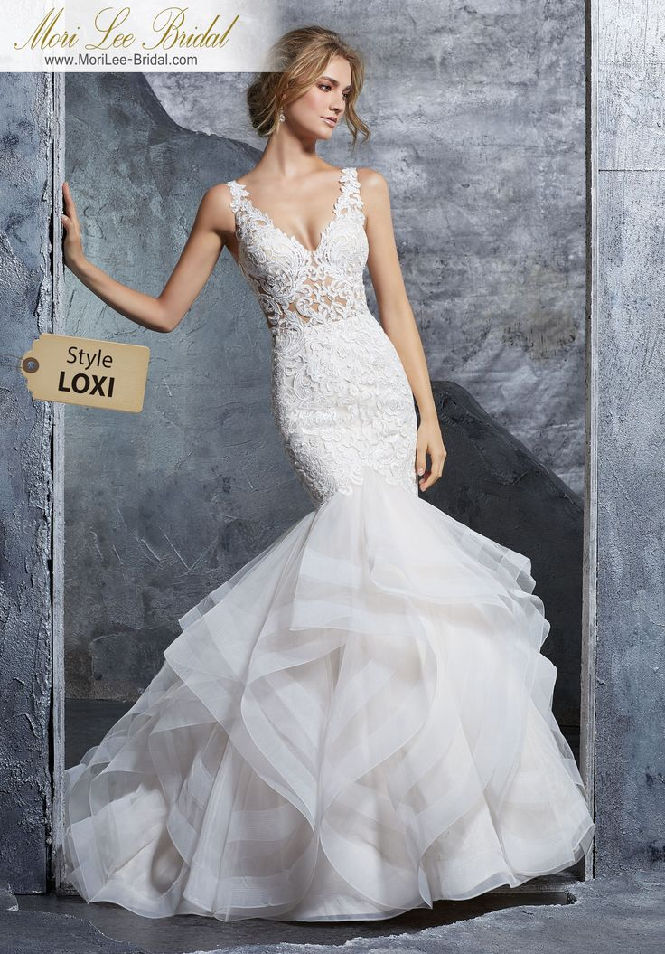 Style LOXI Kayla Wedding Dress Stunning Flounced Tulle Mermaid Featuring a V-Neck Bodice Accented in Sculptured Lace Appliqués. An Open Keyhole Back and Horsehair Trimmed Ruffled Skirt Complete the Look. Matching Satin Bodice Lining Included Available in Three Lengths: 55″, 58″, 61″. Colors Available: White, Ivory, Ivory/Rosé