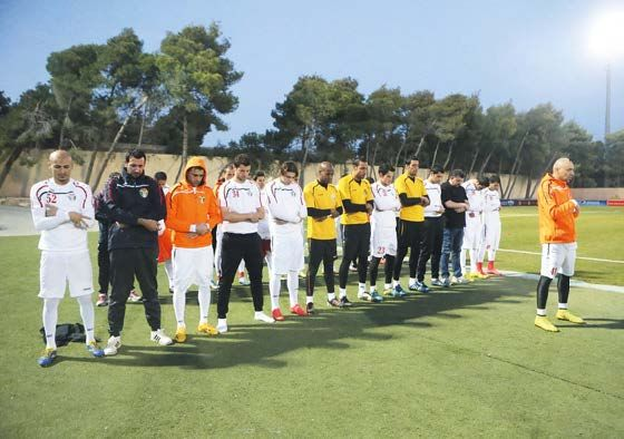 Jordan players line up to pray during a national team training session