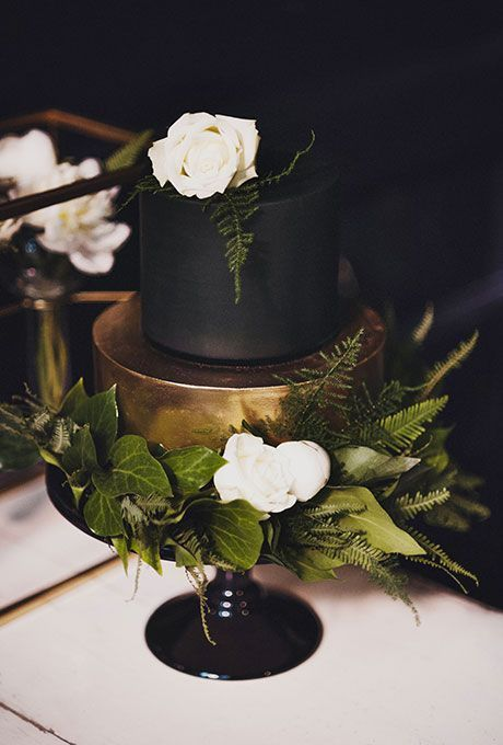 Brides.com: . A two-tiered black-and-gold wedding cake topped with white flowers and greenery, created by Red Bird Cake Company.
