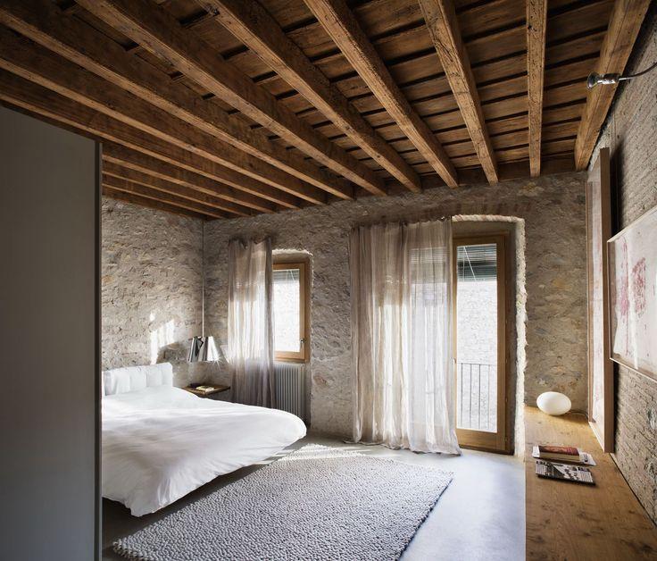 techo de madera y vigas en dormitorio rústico con paredes de piedra