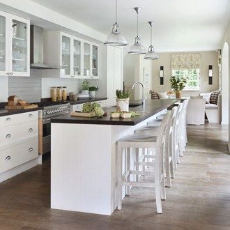 White open-plan kitchen with island, Original BTC pendant lights and window seat
