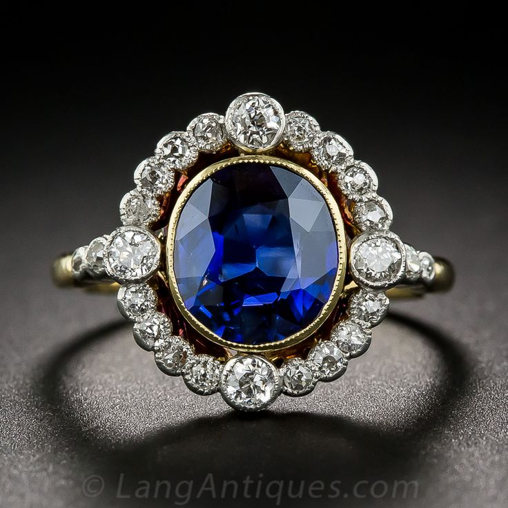 A gorgeous twilight blue sapphire, weighing 1.91 carats, and bearing an AGL certificate stating: 'natural, no evidence of heat or other clarity enhancements, Cambodia origin', is presented with graceful Edwardian-era refinement in this splendid jewel dating from the first decade of the twentieth century. The dusky royal blue gemstone is collet-set in 18K gold and floats inside a sparkling platinum and diamond wreath. A truly elegant and entrancing antique jewel.