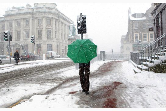 A man in Edinburgh, Scotland, uses an umbrella to shelter from the snow, or is that 'snaw' or 'spitters'?