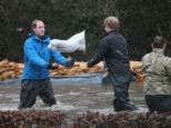 Their Highnesses Princes  William and Harry help stack sandbags for flood ravaged victims of storms in Great Britain 2/14/2014