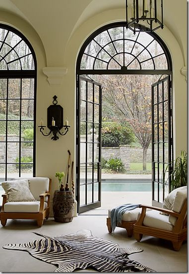 love the balance of traditional cathedral-style steel glass doors + lighting mixed with a modern rug