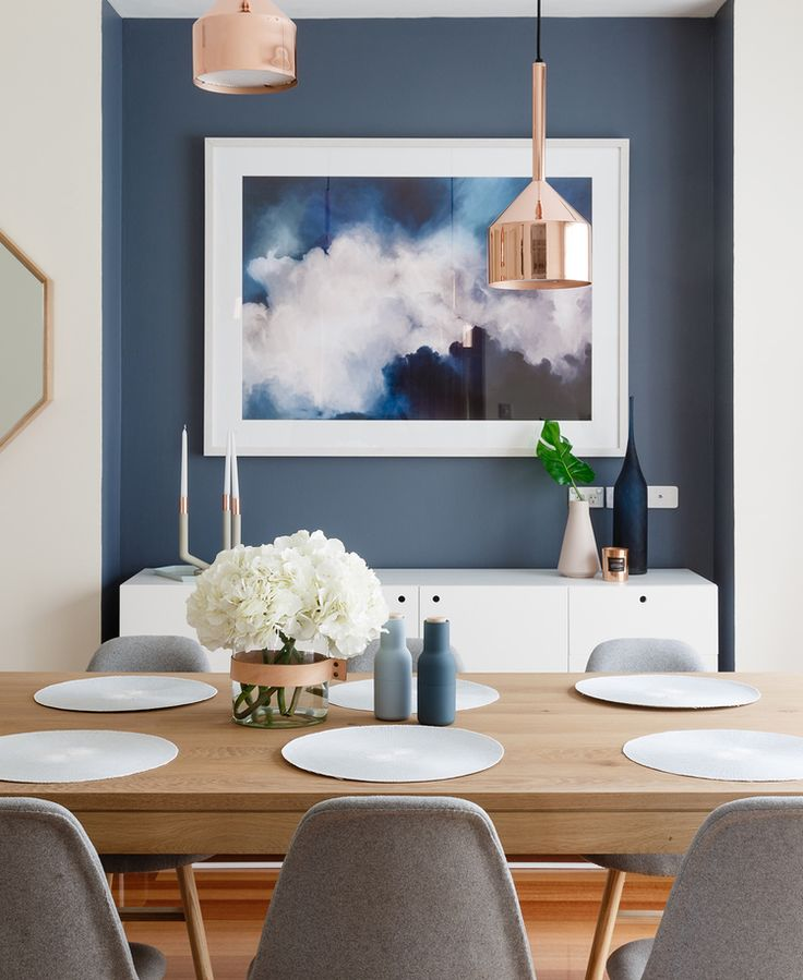 modern scandinavian style dining room with feature blue wall inset with white console, gold pendant lights, gray dining chairs, light wooden dining table