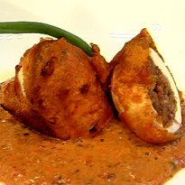 Stuffed Egg Recipe - Eggs stuffed with a mixture of masalas, curd, nuts, cheese and tamarind paste, dipped in batter and fried crisp.