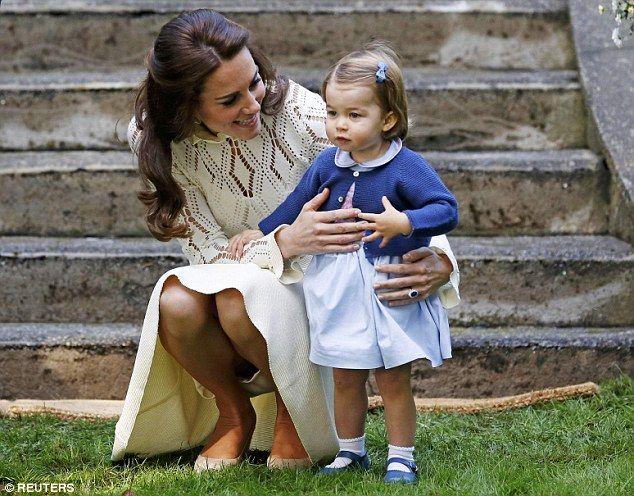 The Duchess of Cambridge, dressed in a cream See by Chloe dress, cuddles Prince Charlotte as they arrive at the party