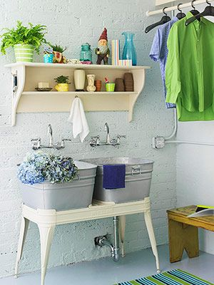 A vintage metal wash stand that has been retrofitted to hold two galvanized basins as sinks.