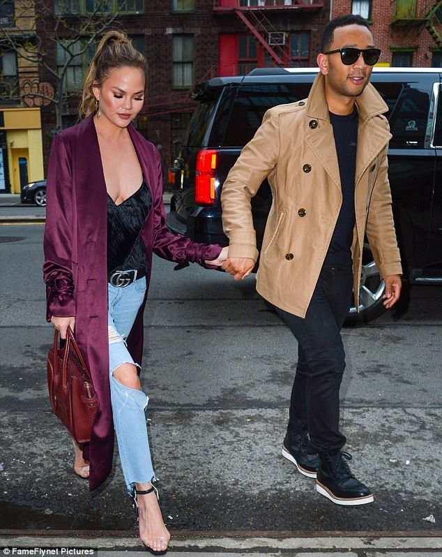 The 30-year-old presenter flaunted her surgically-enhanced assets in a black velvet tank, ripped blue jeans, and translucent stilettos beneath a burgundy silk robe selected by stylist Monica Rose