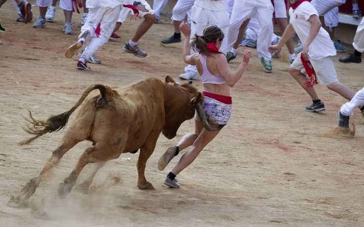 A young woman fails to outrun one of the wild animals during the bull run