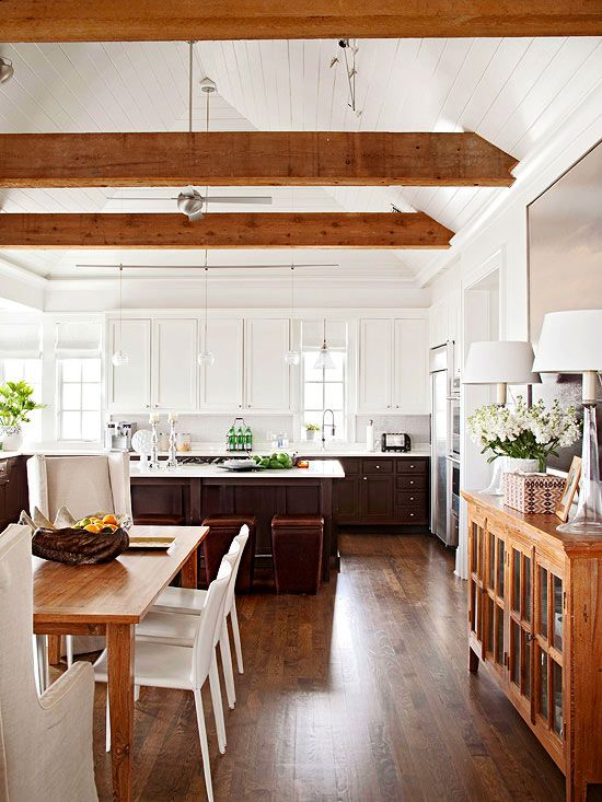 Decorative beams, made to look old using an instant aging technique, add natural appeal to a rustic open dining room. You can readily replicate the effect: Start with newly rough-sawn beams (green wood cracks as it dries). Stain them a dark brown, and then apply whitewash for a mottled look.