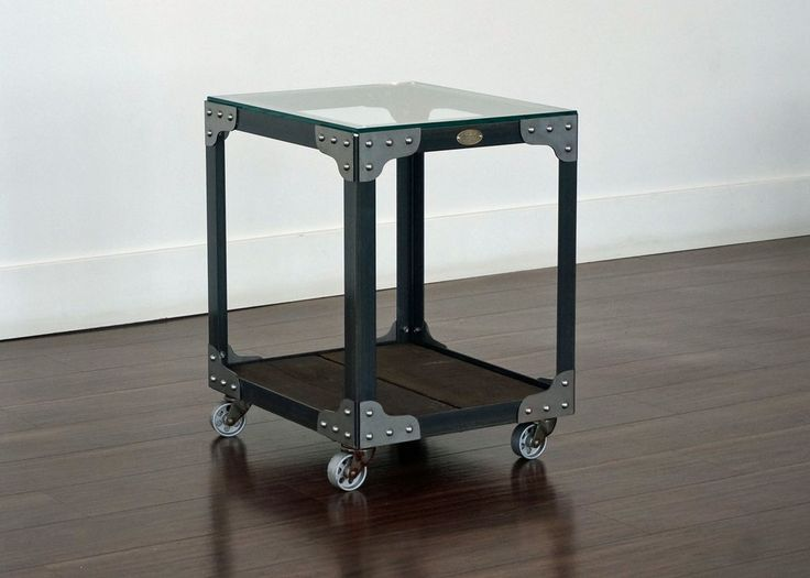 "Aircraft Factory Tool Trolley: Steel & Wood Rustic Industrial End Table mounted on casters with a glass table top - Ideal for Office, Home, Condo, Loft or Cottage Living Room  Features a clear coat steel finish, walnut color wood shelf stain and a clear glass table top.  Fastened with rivets and accent corner brackets, mounted on casters with a decorative vintage style brass boilerplate on front.  18"" W x 20 1/2"" D x 24"" H, 49 lbs.  Duty Free."