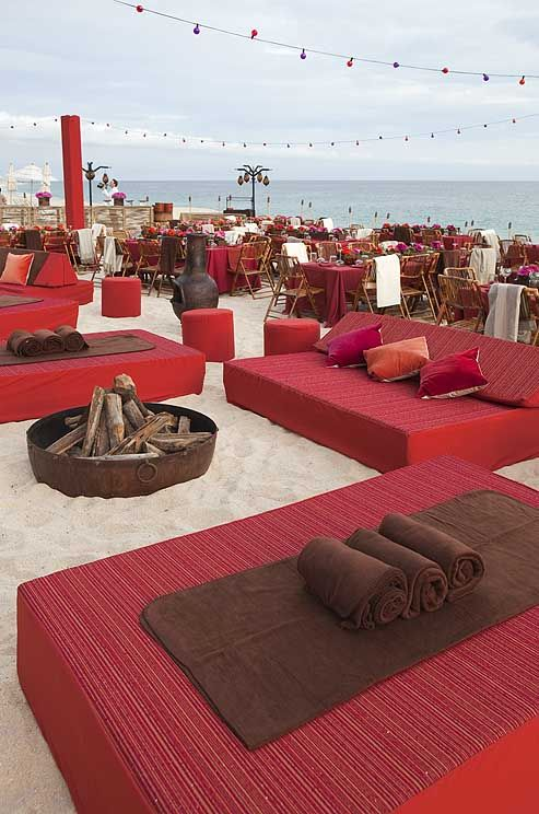 Wow, lovely beach wedding reception set up! For an all-night celebration, couches with red and orange pillows and brown blankets surround metal fire pits.