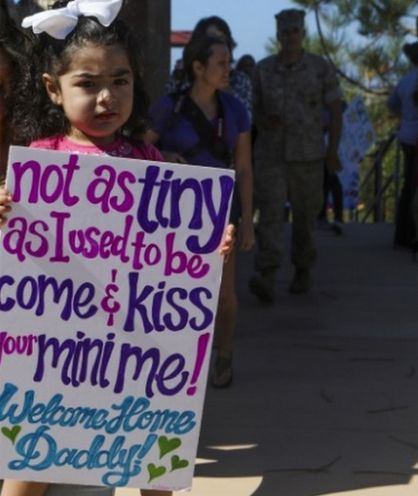 A little girl waits for her Marine daddy returning home from deployment at Camp Pendleton