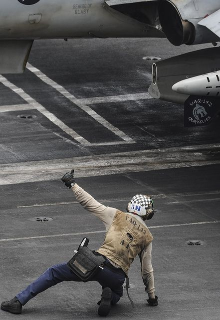 """U.S. 5TH FLEET AOR (Aug. 17, 2013) A Sailor gives a thumbs up as an EA-6B Prowler assigned to the """"Gray Wolves"""" of Electronic Attack Squadron (VAQ) 142 prepares to launch off of the flight deck on board the aircraft carrier USS Nimitz (CVN 68). Nimitz Strike Group is deployed to the U.S. 5th Fleet area of responsibility conducting maritime security operations, theater security cooperation efforts and support missions for Operation Enduring Freedom. (U.S. Navy photo by Kelly M. Agee…"""