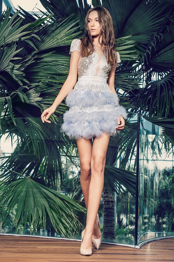 CRISTALLINI SKA342 - Eye-catching and incredible, this fantastic short dress will definitely turn heads at your special party. The fabulous sheer bodice is covered in stunning Chantilly lace with silver threads, embellished with elegant hand-sewn embroidery, beads and sparkling rhinestones and has incorporated push-up bra cups for support. The marvelous skirt features chic hand-sewn embroidery applique and a fabulous array of shimmering swan feathers that float to the mid-thigh hemline with…