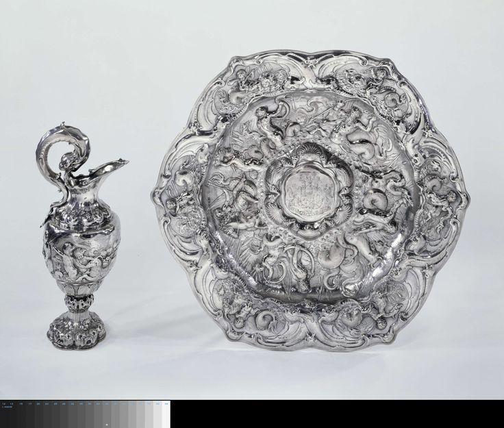 Johannes Lutma (I) | Ewer and basin, Johannes Lutma (I), 1647 | De ronde kan rust op een zeslobbige voet. Deze bestaat uit een lage rechtwandige basis, een gewelfd gedeelte, een glad ingesnoerd middendeel en een gedrukt bolvormige nodus. De lobben aan de onder- en bovenzijde zijn gevormd als uit weke delen opgebouwde maskers. Het eivormige lichaam heeft een ingesnoerd ondergedeelte dat is versierd met palmet-achtige bladeren tegen een achtergrond van weke ornamenten. De wand daarboven is…