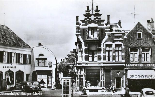 Breda - Haagsemarkt in Princenhage in 1965. Gezien vanuit het zuiden met achter de telefooncel het deel van de Heilaarstraat dat sinds 1972 de Pastoor van Spaandonkstraat heet. Links kledingzaak Nouiwens, rechts op de hoek slagerij Speek, daarnaast drogisterij Elst.