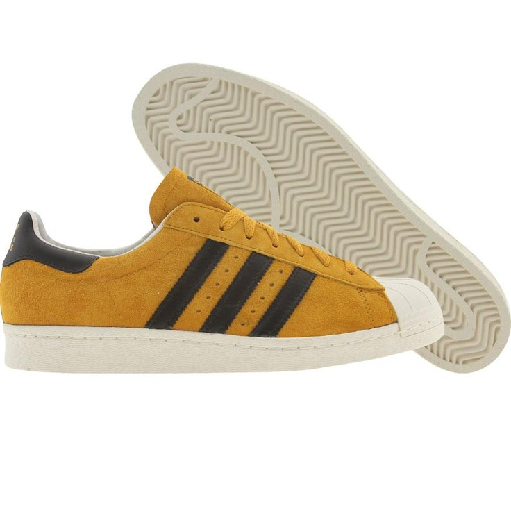 Crayon Gold, black, and legacy Adidas Superstar shoes