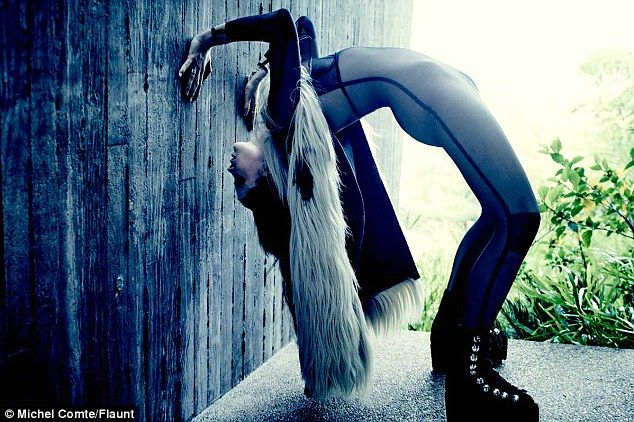 A new perspective: Baldwin bent over backwards in a grey jumpsuit, platform ankle boots, and a fur silver vest