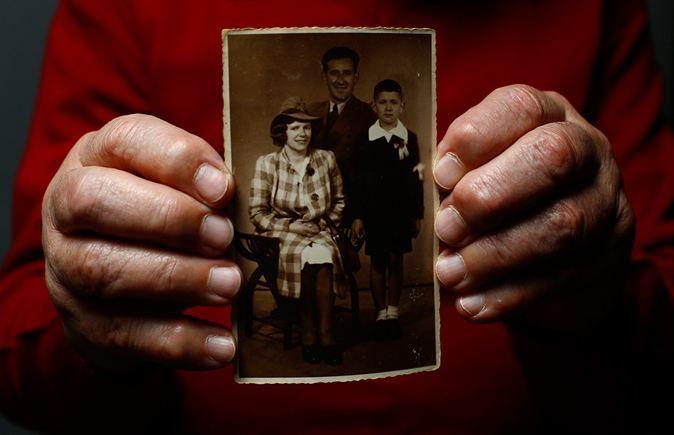 Bogdan Bartnikowski, 82, överlevde fångenskapen i Auschwitz. Här fotograferad av Reuters i december 2014 med ett foto på sin familj. Foto: Kacper Pempel/TT