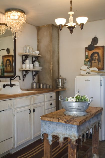 vintage charming kitchen, old wood table and Victorian flashing, one-of-a-kind kitchen island, oil rubbed bronze kitchen faucet, handmade old chandelier frame and crystals, dry brushing, sanding & distressing on column , Ralph Lauren's Glaze tinted in Tea Stain, decorative brackets and shelves.
