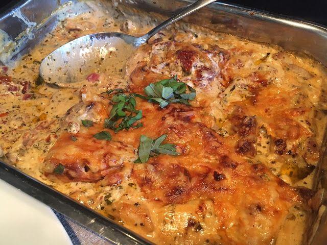 Kip in romige wijnsaus   600 gram kippendijen - 1 grote rode ui  - 3 flinke tenen knoflook  - 200 gram crème fraiche - 200 ml yoghurt of kippenbouillon - 150 ml droge witte wijn - 3 flinke eetlepels Italiaanse kruiden - ca. 1 theelepel pull biber (chilivlokken, toko) - halve pot gedroogde tomaten  - hand geraspte jong belegen kaas (of gratineer kaas, mozzarella) - hand diepvries erwtjes en/of mais - kaas snippers (optioneel) - basilicum (optioneel) - pasta - bouillonblokje, zwarte