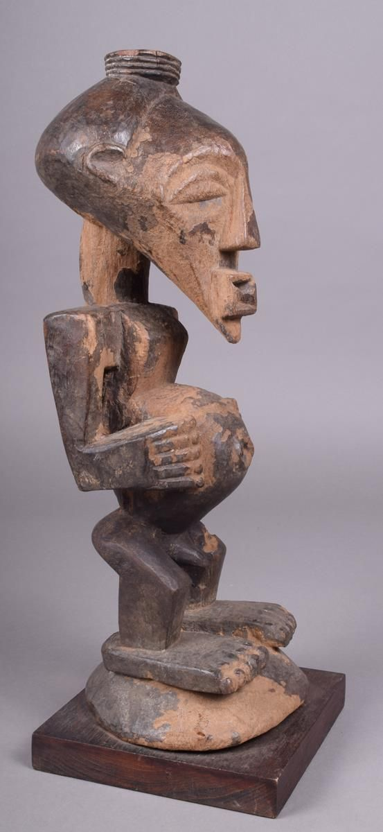 Lot 162 - A Songye fetish figure, D.R. Congo, with pierced head with a ribbed rim, 40cm high, with a stand.