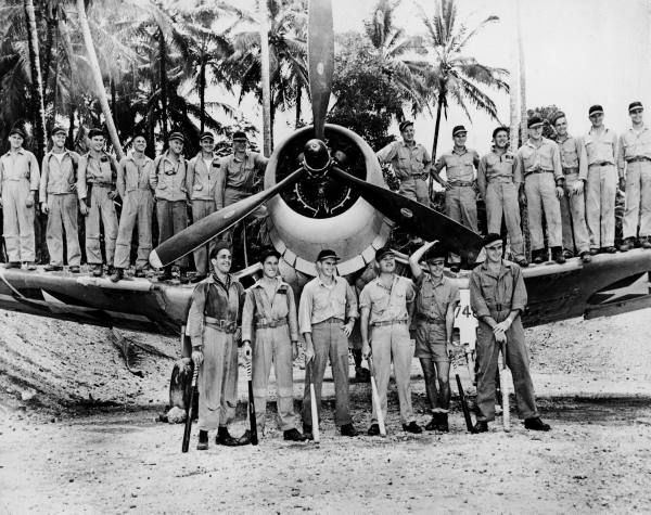 "Marines of the famed VMF-214 Black Sheep squadron wearing baseball caps given them by the St. Louis Cardinals (L-R, front row Christopher Magee, Robert McClurg, Paul A, Mullen, Gregory ""Pappy"" Boyington, John F. Bolt, & Don H. Fisher; (On the wings L-R) Sanders Sims, George Ashmun, Bruce Matheson, James J. Hill, Edwin Olander, Robert Bragdon, Frank E. Walton, Edwin A. Harper, Warren Emrich, William Heier, Burrey Tucker, Donald J. Moore, US Navy flight surgeon James M. Reams & Denmark Grover."