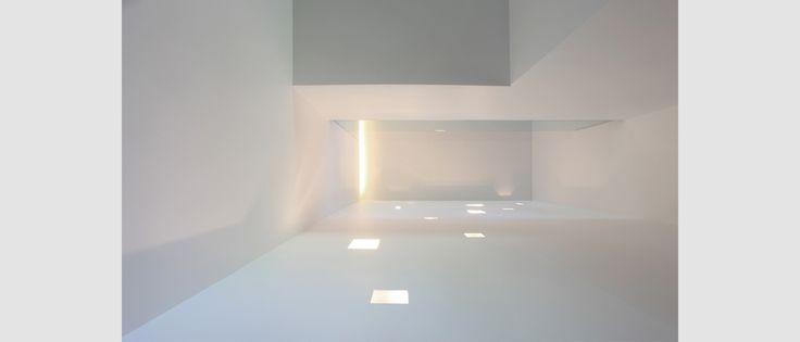 Office Extension in Riemst. (Belgium) De leefruimte wordt voorzien van twee zitkamers die 'verbonden' worden met een doorkijkhaard. Eén zitkamer, hoger in ruimte gedimensioneerd, ontvangt enkel bovenlicht en heeft hierdoor een besloten karakter. De andere zitkamer wordt gericht op het open veldlandschap alsook op de eetruimte en de keuken, die in één ruimte wordt vormgegeven. Het binnenraam op de nachtoverloop, dat
