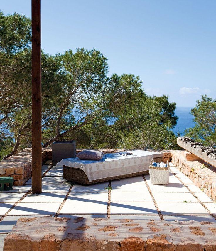 Шезлонг из ротанга на выступе террасы позволяет загорать наслаждаясь видом на море.  (средиземноморский,архитектура,дизайн,экстерьер,интерьер,дизайн интерьера,мебель,на открытом воздухе,патио,балкон,терраса) .