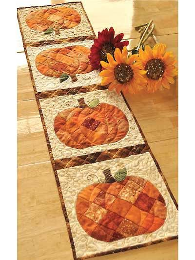 """Get ready for autumn with this cute harvest table runner!   Use your favorite orange scraps to complete this cute project. This sophisticated fall decoration features patchwork pumpkins, appliqued stems and leaves and just a touch of embroidery.   Finished size table runner is 12 1/2"""" x 53"""" and uses 14 (2 1/2"""") strips or 100 (2 1/2"""") squares."""