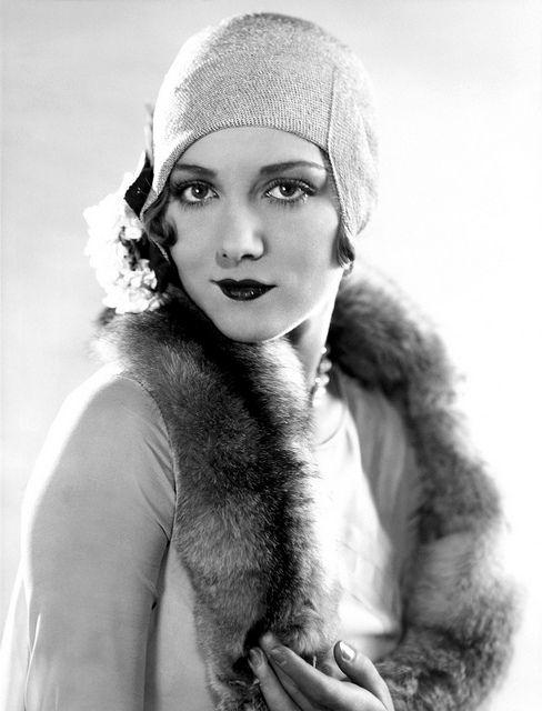 El sombrero cloche, el corte bob, las perlas, las pieles, las cejas depiladas, el maquillaje marcado..... todo el estilo de una flapper.