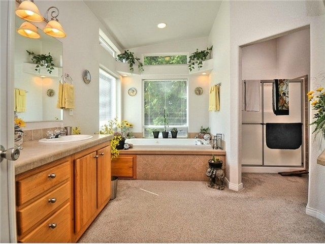 French doors lead to master bath suite with soaking tub, shower, wc and two vanity counters.