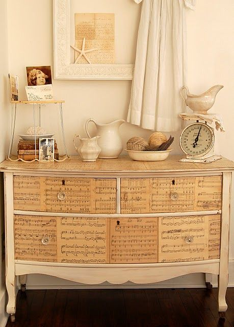 Sheet music on a lovely painted chest. Have done this with a suitcase, a wooden thing with small drawers would also be nice.