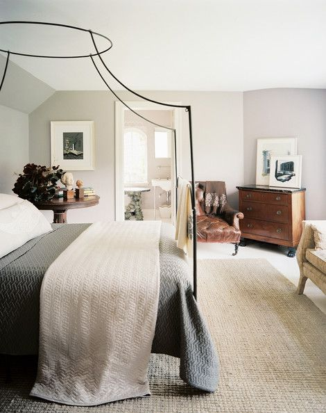 A delicate iron canopy bed in a guest room. I like the combination of modern