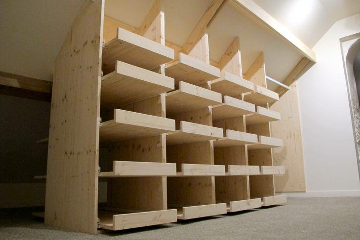 Fabrication et installation d'un dressing en épicéa. Toutes les tablettes sont montées sur des coulisses à grande course permettant d'accéder à la pile de vêtements située à l'arr…