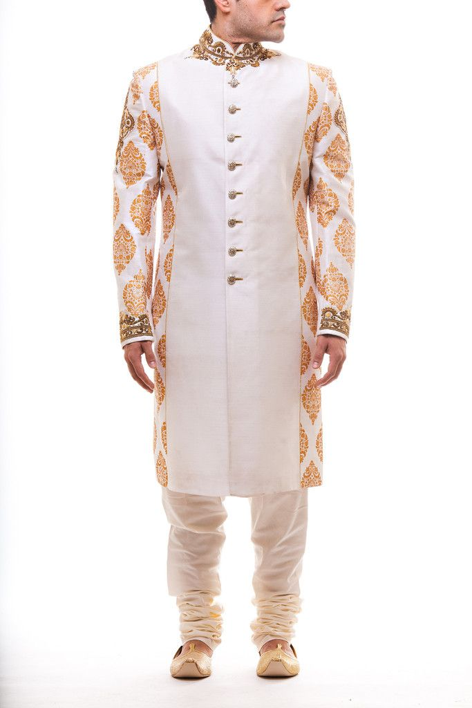 White and gold block print achkan with a raw silk middle panel and embroidered collar and cuff and matching white churidar pajami. Stole sold separately.