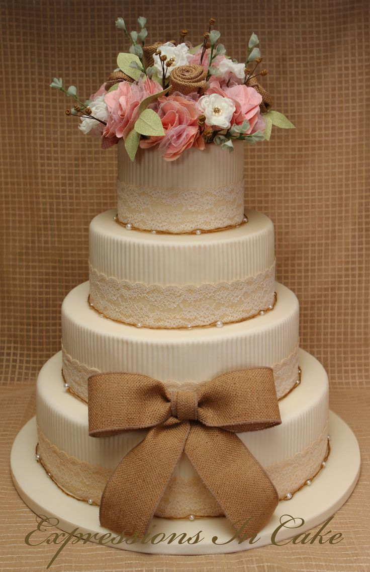 Rustic, country chic wedding cake.  Features handmade fabric flowers, a burlap bow, and jute & pearl string borders.  Tea-stained fabric lace around each tier.  https://www.facebook.com/pages/Expressions-in-Cake/286620766001?ref=ts=ts