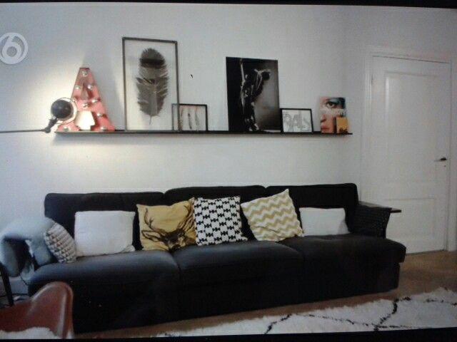 Balkje met schilderijen boven de bank en zwart/wit/oker gele kussens met print (vtwonen.nl aflevering 7 feb ' 16)
