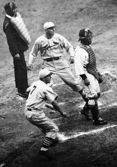 St. Louis Cardinals pitcher Dizzy Dean center looks up as he crosses the plate in the third inning of the World Series game seven against the Detroit Tiger played in Detroit on Oct. 9 1934. Dean was one of three runners to score on a double by player/manager Frankie Frisch. The Cardinals also known as The Gashouse Gang won the game 11-0 to capture their third World Series title. Dean was the winning pitcher in the game his second victory of the series. (AP Photo)