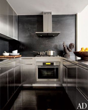 кухня из стали, плинтус из затемнен. стали  stainless-steel cabinetry and a blackened-steel backsplash; the carved folk-art rooster is 19th century
