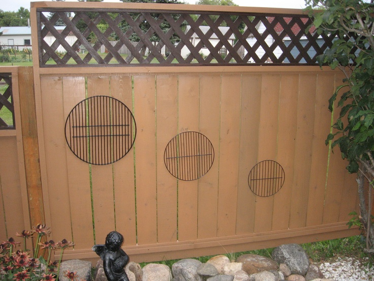 recycled bbq grills, sanded, spray painted voila! outdoor fence art