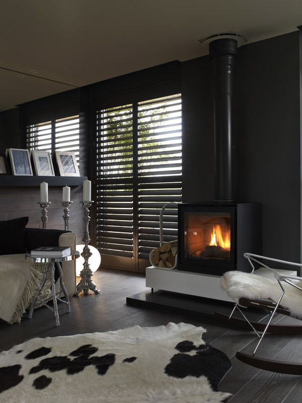 I'll pass on the cow rug, but there's is nothing quite like a dark cozy space with an option for natural light. Black/Dark walls for the win.