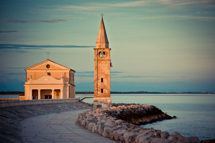 Lighthouse and church in Caorle, Veneto region. (Italy)