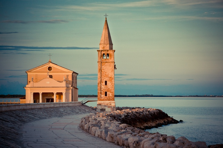 Lighthouse and church in Caorle, Veneto region. (Italy)
