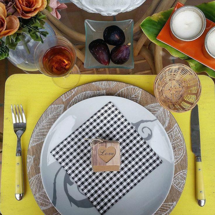 servilletas de cuadritos de vichy negros y blancos sobre plato blanco con detalle en gris, y bajoplato de madera con hojas blancas