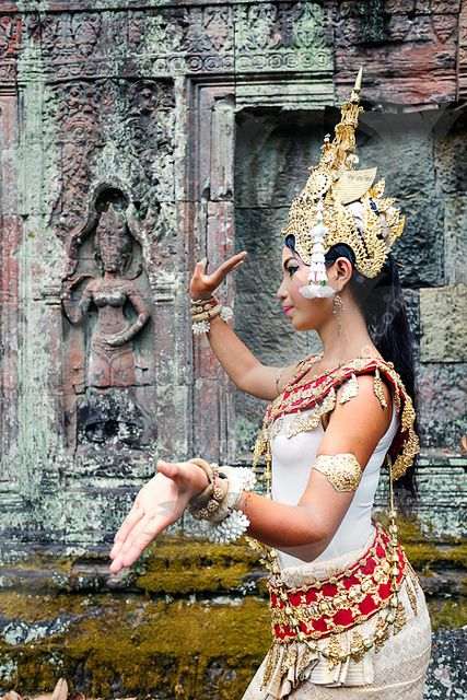 Modern Apsara dancer with ancient Apsara portrayed on wall | Apsaras are female spirits or celestial nymphs in Hindu and Buddhist mythologies. They're young, beautiful, magical and, not surprisingly, excellent dancers. Apsara dances tell classical myths inspired by the Cambodian version of the Ramayana and Angkor's golden age (889–1434) when its major temples — Angkor Wat, Bayon and Ta Prohm — were built. Khmer Apsara dancer, Angkor Wat, Cambodia